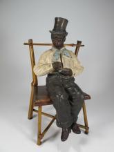 Antique terracotta black man statue & a bamboo chair