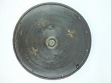 A 19th Century Abyssinian hide shield, 56cm diameter body of characteristic form incised with concentric bands of incised geometric and linear decoration, white metal central boss and further applied white metal crosses, one lacking, hide handle to