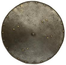 A 17th Century etched Italian shield, the 62cm diameter mildly convex body with turned edge and sparse domed brass rivet decoration, eight further domed rivets for the braces, etched foliate swirl emanating from the central domed boss, further
