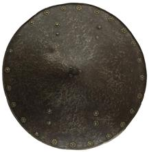 A 16th Century German shield, the 56cm diameter heavy gauge slightly convex body rising to a square section spike finial, dished edge surrounded by domed rivets with embossed foliate brass washers, one lacking and two partial, eight further domed