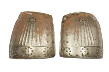 A pair of 17th Century North European Tassets, each composed of two hinged lames, one large and one small, each with turned edge, each tasset with narrow side gullies and broad lower gullies, all with faceted rivet decoration, each tasset with a