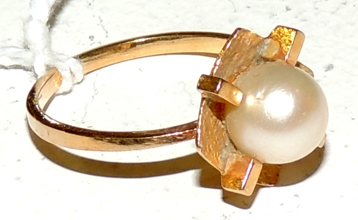 CULTIVATED PEARL RING in yellow tinged gold and staple detail.