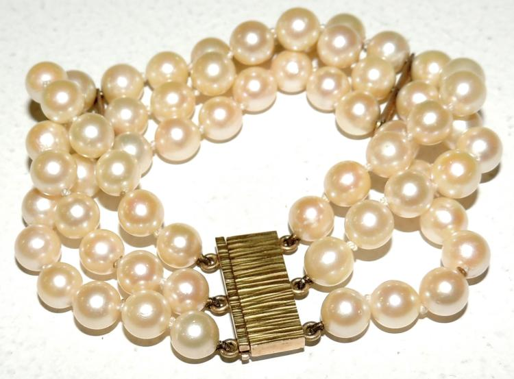 BRACELET OF THREE STRIPS OF CULTURED PEARLS with zipper and yellow gold dividers.