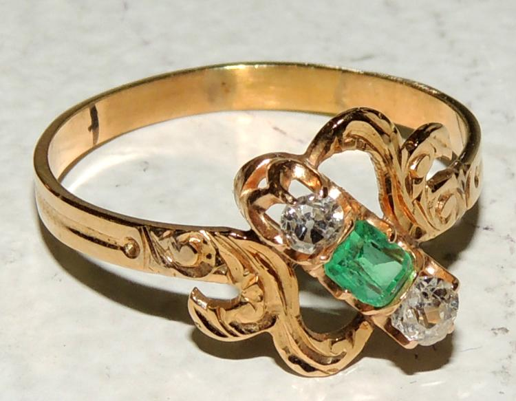 RING in 18kt yellow gold flat ribbed arm with floral design and claw mounts with natural emerald and two diamonds. With gemological assessment report.