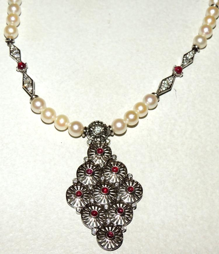 NECKLACE OF RUBY, PEARLS AND DIAMONDS with a central pendant in the style of openwork rosettes with cabochon ruby tips.Strip of pearls alternated by diamond-shaped details of diamonds and rubies in white gold.With safety chain.Total length: 24 cm.