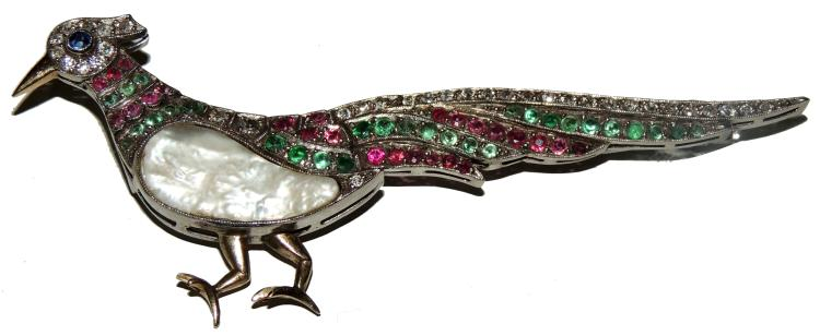BROOCH as a bird of brilliants, emeralds and rubies with sapphire detail and mother-of-pearl body.White gold frame, beak and legs in yellow gold.Length: 7.8 cm.