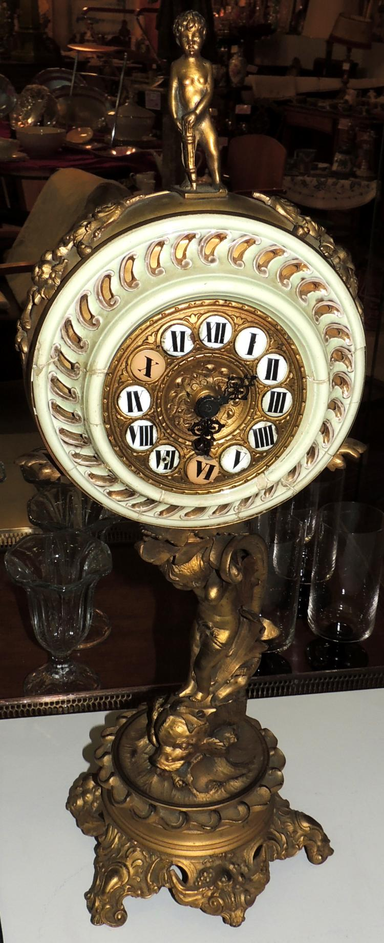 DESKTOP CLOCK in bronze figure as a column with enamel decoration.Missing cap and key.Height: 57 cm