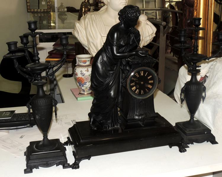CLOCK WITH GUARNITION in patinated metal with black marble base. With pendulum. Candelabra fittings of 4 lights with a cup-like shaft and marble base. Height fittings: 50 cm. Measures watch: 56x41x19 cm.