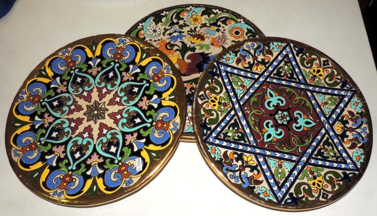 THREE SEVILLAN PLATES in enameled ceramic with different motives in bright colors.One with desp.Diameter: 27 cm