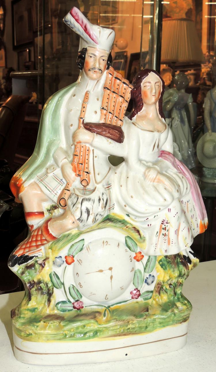 PAIR OF FIGURES in Staffordshire porcelain in the shape of a clock.Height: 34 cm