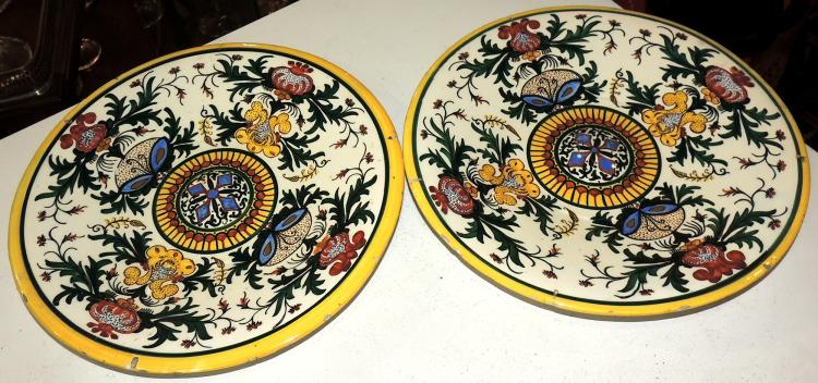 PAIR OF DECORATIVE DISHES late 19th century in enameled pottery painted with plant decoration in bright colors. Diameter: 29 cm.