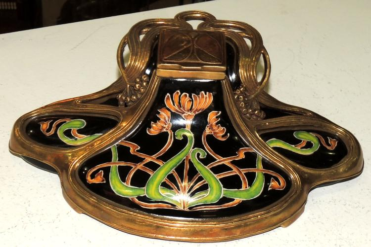 MODERNIST INKWELL in ceramics and bronze with vegetal decoration.Marks on the base dated 1906. Measurements: 7x22 cm.