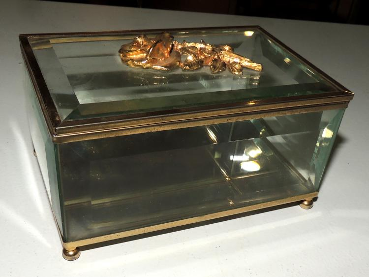CAJA-JOYERO in beveled glass and gold metal. With application of floral detail. It supports on four lentil legs. Measures: 8x15x10 cm.