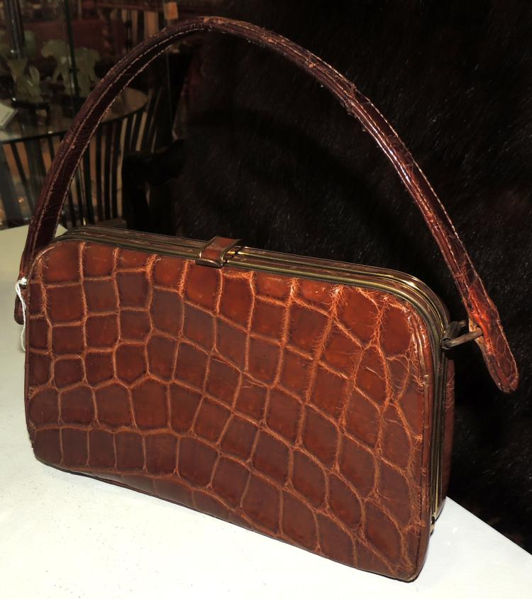 HANDBAG in brown crocodile leather with suede lining and interior departments.With a handle.Lig.chafing