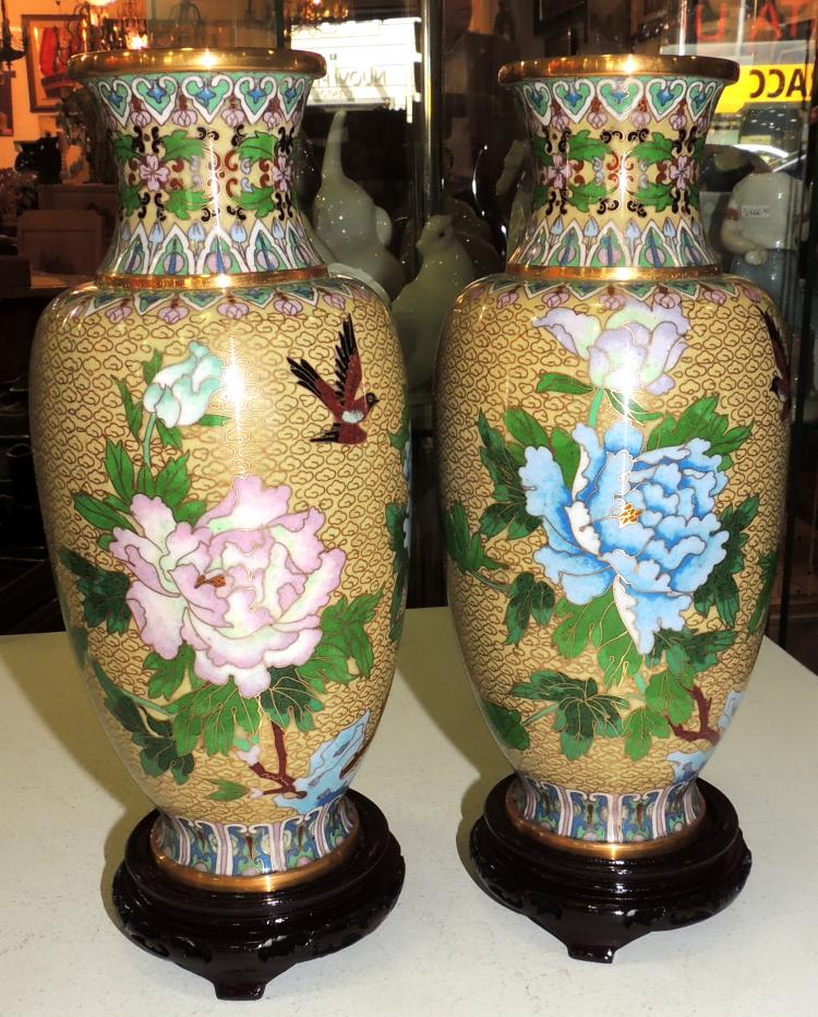 COUPLE OF ORIENTAL VASES in cloisonné enamel with flower decoration on yellow background.With wooden bases.Total height: 29 cm.
