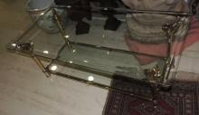 AUXILIARY TABLE in gold metal topped with elephant heads with bezel in glass on two levels.Measures: 40x110x55 cm.