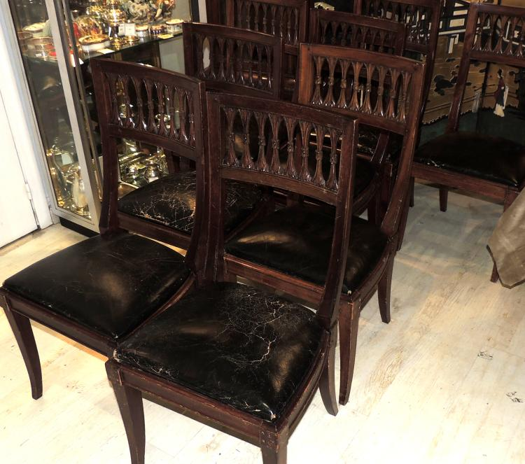 SET OF EIGHT CHAIRS in wood with openwork backs and seats upholstered in black leather, lig desp.