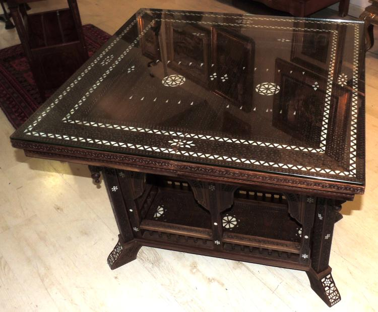 ARAB GAME TABLE carved with marquetry in mother-of-pearl and on glass.Base in the form of arabesque windows with gallery.Measures: 77x84x84 cm.
