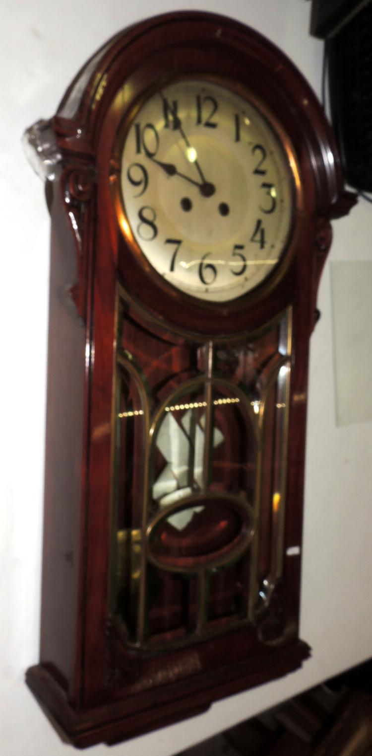 WALL CLOCK in mahogany wood with pendulum and key.Measures: 75x40 cm.