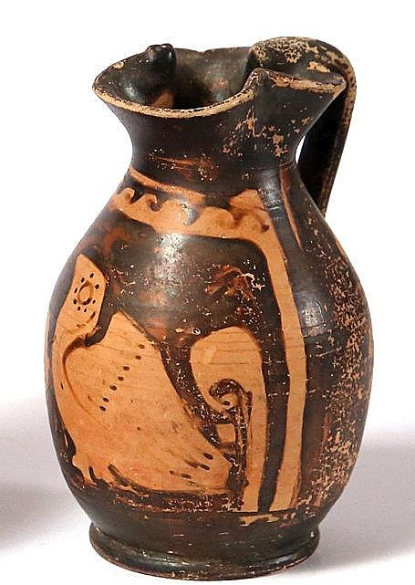 A CAMPANIAN TERRACOTTA JUGLET 4th century BCE. 10.5 cm high. With barrel-shaped body and trefoil l