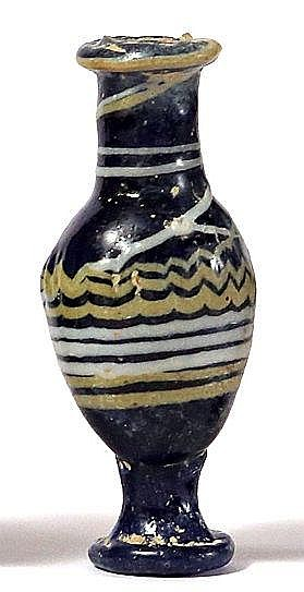A CORE-FORMED GLASS UNGUENTARIA  3rd-2nd century BCE. Of cobalt blue color with yellow and white dec