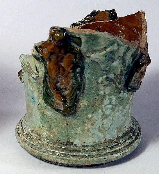 THE LOWER PRESERVED PART OF A GREEN AND YELLOW GLAZED POTTERY KALATHOS WITH APPLIED RELIEFS