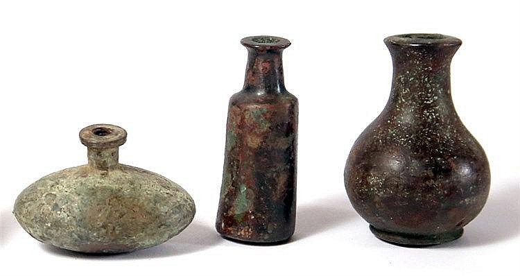 THREE BRONZE COSMETIC BOTTLES 2nd-1st millennium BCE. In good condition. 5.9, 5.8 and 3.5 cm high. E