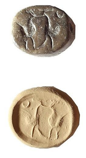 A SCARABOID SEAL Iron Age, 8th-7th century BCE. Depicting two roosters and a crescent. In good