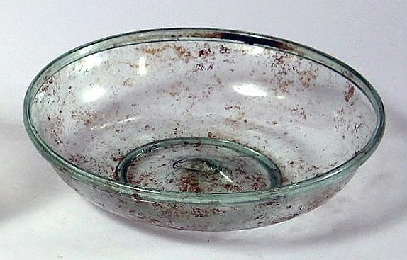 A TRANSLUCENT GREEN GLASS BOWL Roman Period, 2nd-4th century CE. With folded rim and ring base.