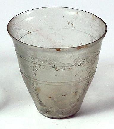 A TRANSLUCENT GLASS BEAKER 2nd-3rd century CE. With V-shaped body and three external wheel-cut bands