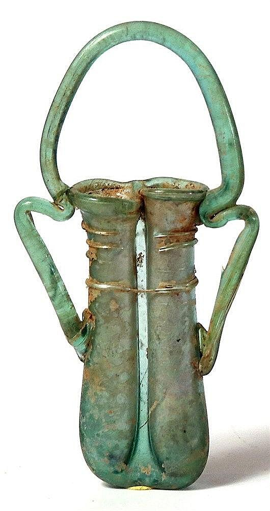 A GREEN GLASS DOUBLE UNGUENTARIA Byzantine Period, 4th-5th century CE. The basket handle is men