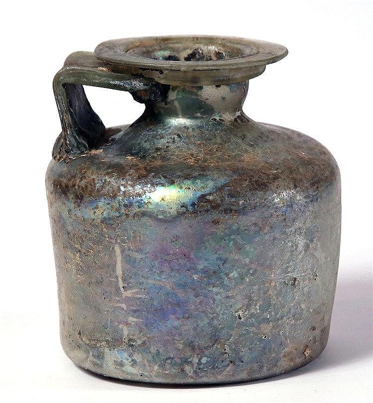 A ROMAN CYLINDRICAL GLASS BOTTLE  1st-2nd century CE. With squat body and broad handle. With a crack