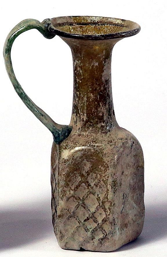 A PENTAGONAL YELLOW GLASS JUGLET Ca. 6th century CE. Body blown into a mold, each side depicts