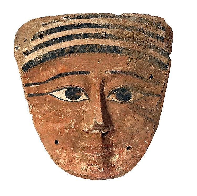 AN EGYPTIAN WOODEN COFFIN MASK New Kingdom, 1550 – 1070 BCE. A flat-section carved mask, covere