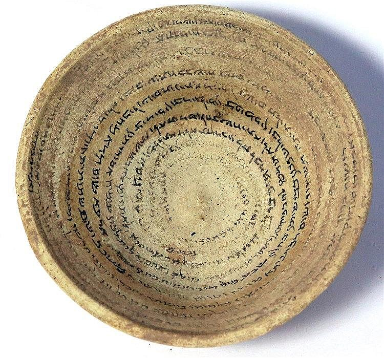 A TERRACOTTA INCANTATION BOWL 5th-6th century CE. 15.7 cm in diameter. The Aramaic text starts with