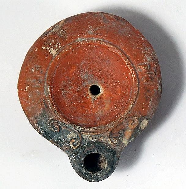 A ROMAN TERRACOTTA OIL LAMP 2nd-3rd century CE. With red slip and a rosette on the base. In very go