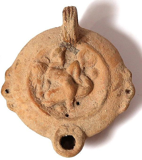 A ROMAN TERRACOTTA OIL LAMP DEPICTING CUPIDON RIDING A DOLPHIN 1st-2nd century CE. Handle mende