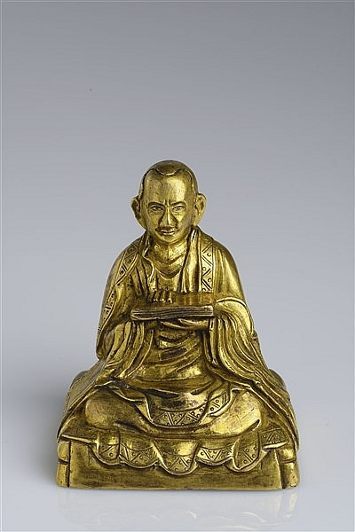 A GILT BRONZE FIGURE OF A GURU