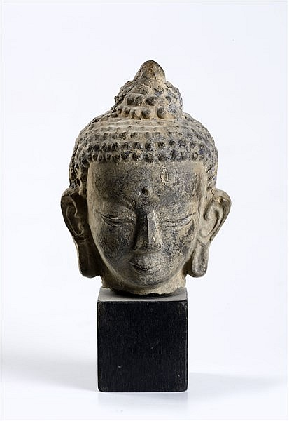 AN EARTHENWARE HEAD OF BUDDHA