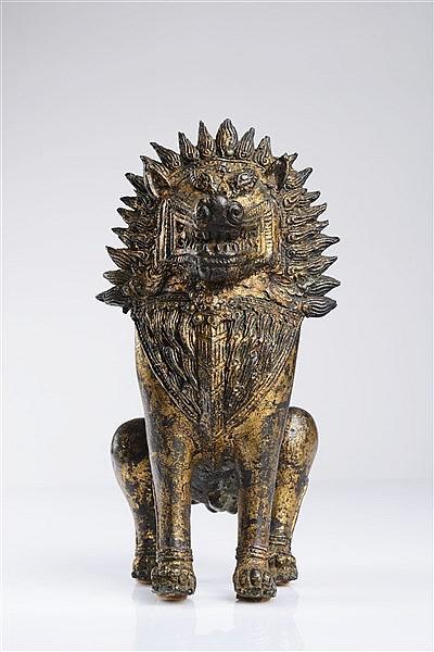 A GILT BRONZE FIGURE OF A TEMPLE GUARDIAN LION