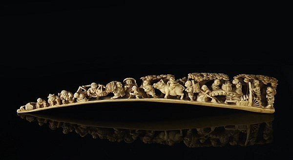 A CARVED IVORY OKIMONO WITH GENRE SCENES