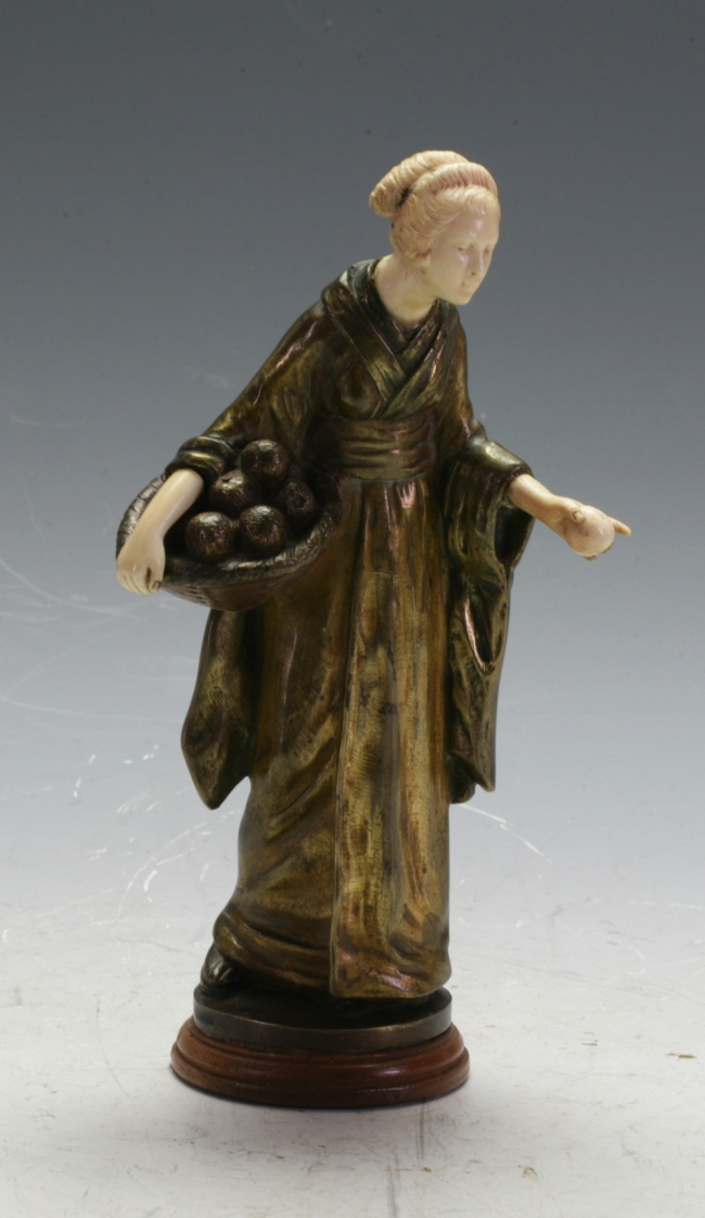 A Japanese bronze and ivory figure
