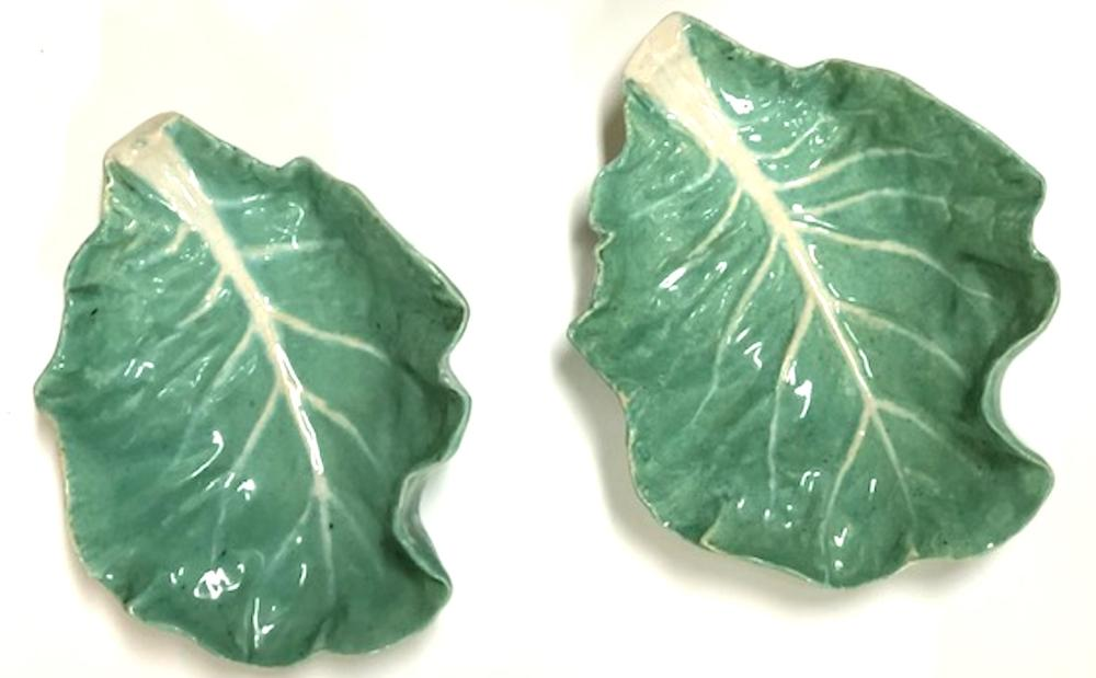 A pair of green glazed cabbage leaf faience plates, Continental circa 1920