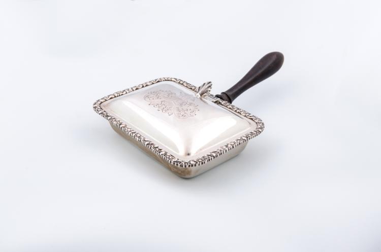 Vassoio per pane caldo in argento sbalzato e cesellato con manico in legno ebanizzato | Embossed and engraved silver tray for hot bread with ebonized wooden handle.