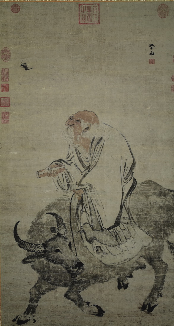 A CHINESE SCROLL PAINTING OF A MAN RIDING A COW