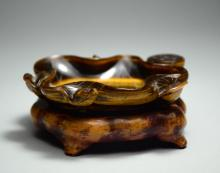 A TIGER EYE INK STONE WITH WOOD STAND