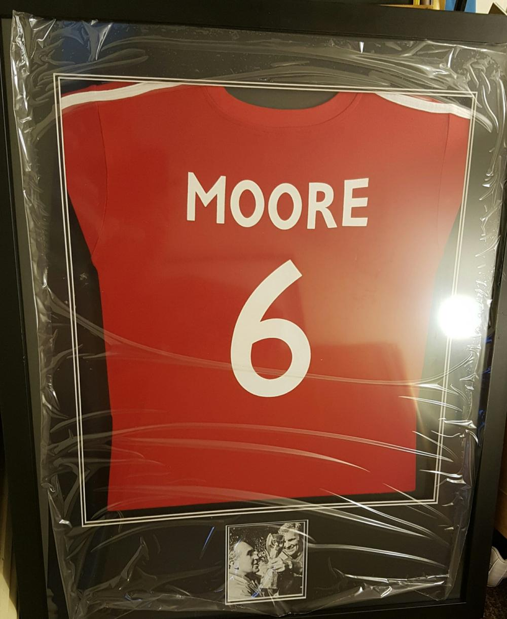 Lot 19 - Bobby Moore item containing replica red England Shirt and a signed black and white picture of Bobby Moore lifting the World Cup Trophy