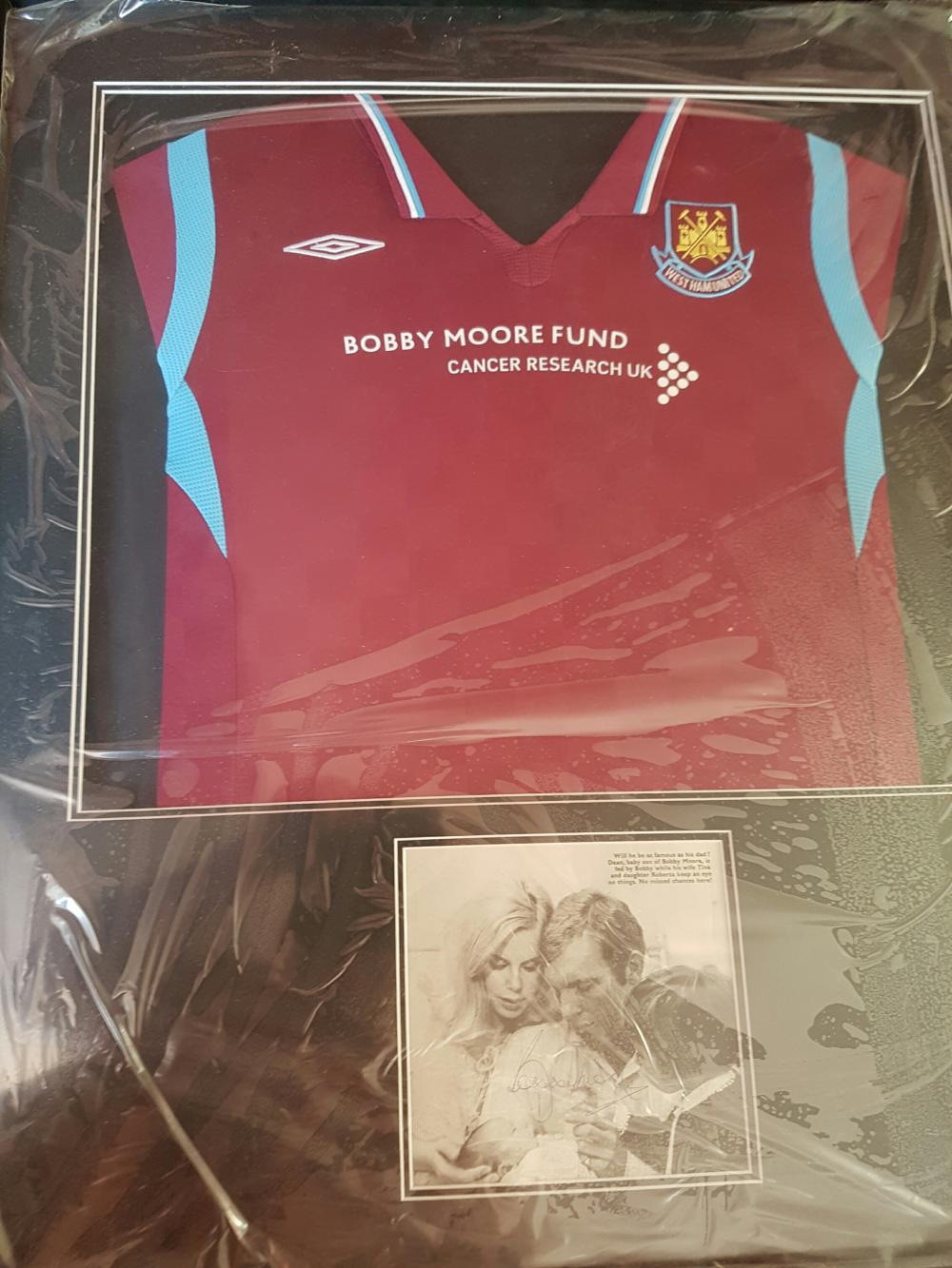 Lot 21 - Framed West Ham Shirt along with a Signed picture of England World Cup 1966 Winner Bobby Moore (Holding his Baby) - Robert Frederick Chelsea Moore OBE (12 April 1941 24 February 1993) was an English professional footballer. He captained