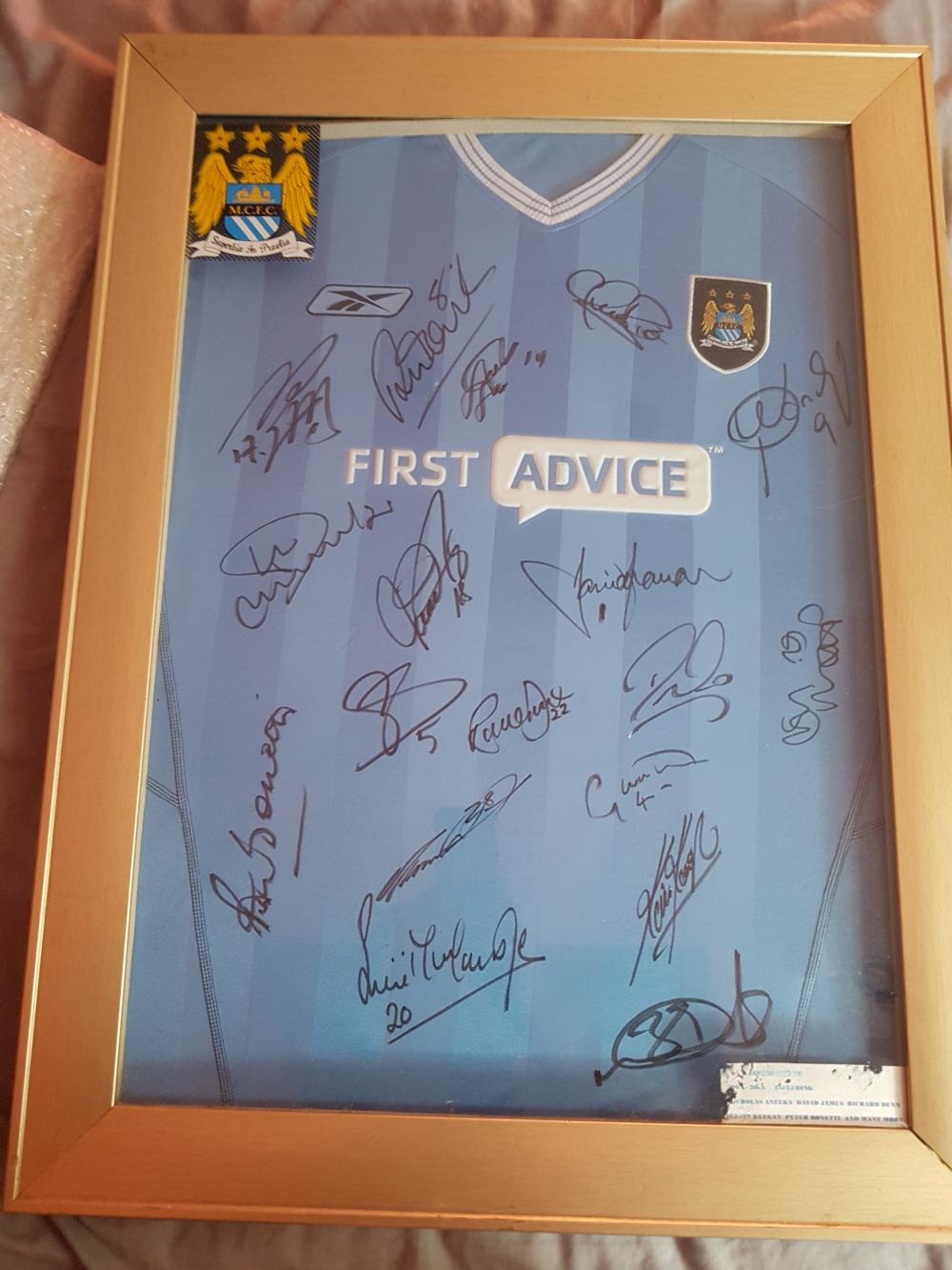 Lot 76 - Signed and Framed Manchester City Football Shirt (Sponsor First Advice), which is signed by the Team.