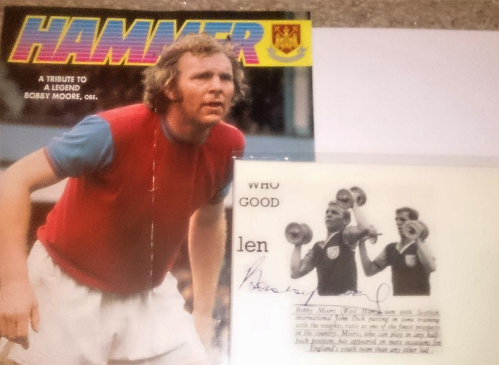 "Lot 83 - Signed Bobby Moore paper cutting plus programme. Robert Frederick Chelsea """"Bobby"""" Moore OBE (12 April 1941 to 24 February 1993) was an English professional footballer."